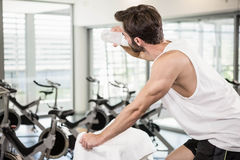 Fit man on exercise bike drinking water Stock Photos