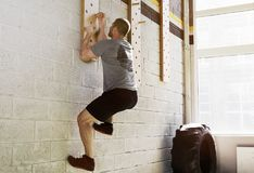 Man exercise on peg board in gym. Fit man exercise on peg board in gym royalty free stock images