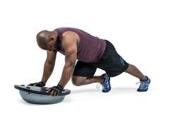 Fit man exercising with bosu ball Stock Photos