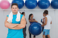 Fit man with friends in background at fitness studio Royalty Free Stock Image