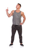 Fit Man In Gray Tank Top And Camo Pants Looking Up And Pointing Royalty Free Stock Image