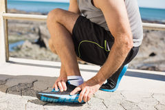 Fit man gripping his injured ankle Royalty Free Stock Images
