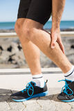 Fit man gripping his injured calf muscle Stock Photos