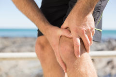 Fit man gripping his injured knee. On a sunny day Stock Photo