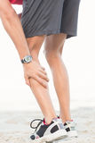Fit man having muscle pain. At the beach Stock Photos