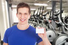 Fit man holding blank visiting card. Young Healthy Athletic Man Holding Blank Visiting Card At Gym Stock Image