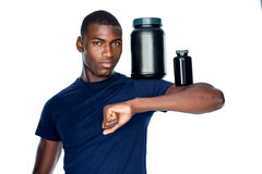 Fit man holding bottles with supplements on his biceps Stock Images