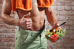 Fit man holding a bowl of fresh salad on old red bricks background Royalty Free Stock Images