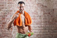 Fit man holding a bowl of fresh salad on old red bricks background Stock Images