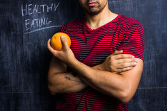 Fit man holding a grapefruit in front of blackboard Royalty Free Stock Image