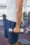 Fit man holding heavy dumbbell Stock Image