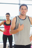 Fit man holding water bottle with friend in background in exercise room Royalty Free Stock Photography