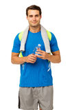 Fit Man Holding Water Bottle. Portrait of fit young man holding water bottle standing isolated over white background. Vertical shot Stock Photography