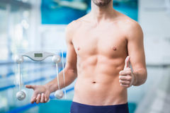 Fit man holding a weighting scale with thumbs up Stock Photos