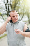 Fit man jogger listening music by earphones. Stock Photo
