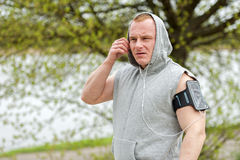 Fit man jogger listening music by earphones. Stock Images