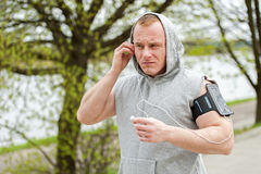Fit man jogger listening music by earphones. Stock Photos