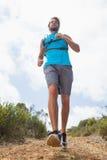Fit man jogging down mountain trail Stock Photo