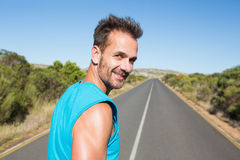 Fit man jogging on the open road smiling at camera Royalty Free Stock Image
