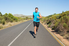 Fit man jogging on the open road Stock Image