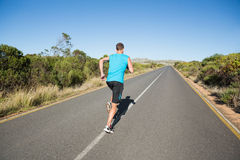 Fit man jogging on the open road Stock Photos