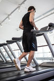 Fit man jogging on the treadmill Stock Images