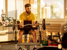 Fit man lifting dumbbells at  gym Royalty Free Stock Photo