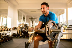 Fit man lifting dumbbells at  gym Royalty Free Stock Photography
