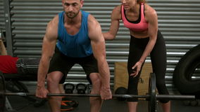 Fit man lifting dumbbells with trainer. In crossfit stock footage