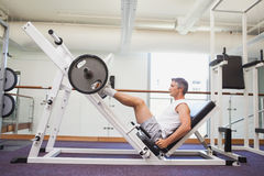 Fit man lifting heavy barbell with legs Stock Photography