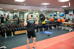Fit man lifting heavy barbell in weights room Stock Photo