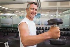 Fit man lifting heavy black dumbbell Stock Photo