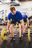 Fit man lifting weights at the gym. Stock Image