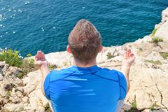 A fit man in the Lotus position on a seashore. Young fitness man doing yoga outdoors. Stock Photos