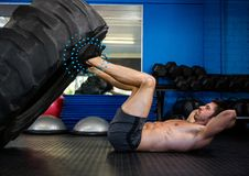 Fit man performing leg press with tire in gym against spiral dots in background. Digital composition of fit man performing leg press with tire in gym against Stock Images