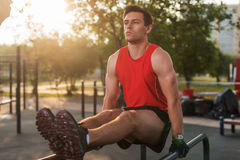 Fit man performing leg raises on outdoor fitness station. Fit man performing leg raises on outdoor fitness station stock image