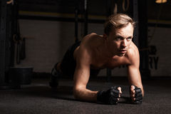 Fit man planking in gym. To strengthen his core Stock Images
