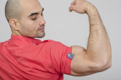 Fit man posing with his arm up showing his biceps. Stock Photos