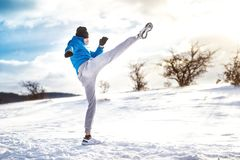 Fit man practicing a kick shot outdoor in snow. Fitness player training Royalty Free Stock Photography