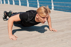Fit man pushing up on pier. Confident man doing push-ups on esplanade at the sea. Horizontal outdoors shot Royalty Free Stock Photos