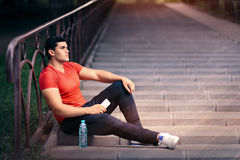 Fit Man Resting with Water Bottle and Phone Stock Photo