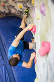 Fit man rock climbing indoors Stock Photos