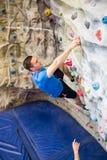 Fit man rock climbing indoors Royalty Free Stock Image