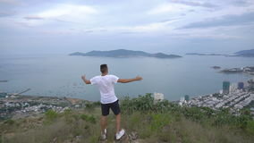 Fit man runner happy and celebrating success. Male stand on top of the mountain, cheering in winning gesture. Beautiful. View of Nha Trang city, Vietnam stock video