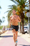 Fit man runner training cardio running in city. Handsome young male adult in his 20s jogging shirtless during warm summer day on a sidewalk in tropical urban Royalty Free Stock Photo