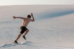 Fit man running fast on the sand. Powerful runner training outdoor on summer. stock image