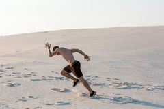 Fit man running fast on the sand. Powerful runner training outdoor on summer. Stock Photos