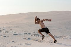 Fit man running fast on the sand. Powerful runner training outdoor on summer. Royalty Free Stock Photos