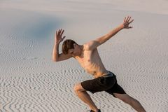 Fit man running fast on the sand. Powerful runner training outdoor on summer. Stock Photo