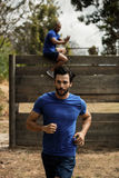 Fit man running during obstacle course Stock Photo